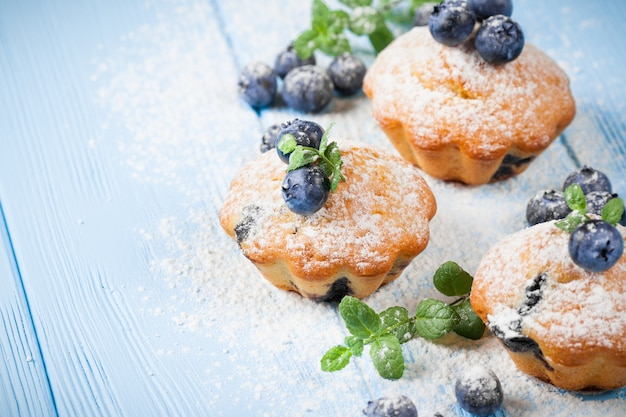 フルーベリーマフィン。ブルーベリー、新鮮な果実、木製の背景にミントの自家製焼きたてのカップケーキ。