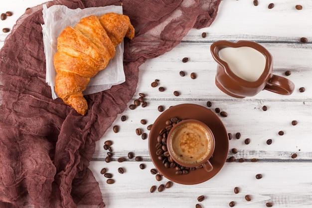 茶色のナプキン、クリーム、焼きたてのクロワッサン、白い木製の背景にセラミック皿にコーヒーのカップ。朝食に焼きたてのペストリー。美味しいデザート。クローズアップ写真。水平バナー