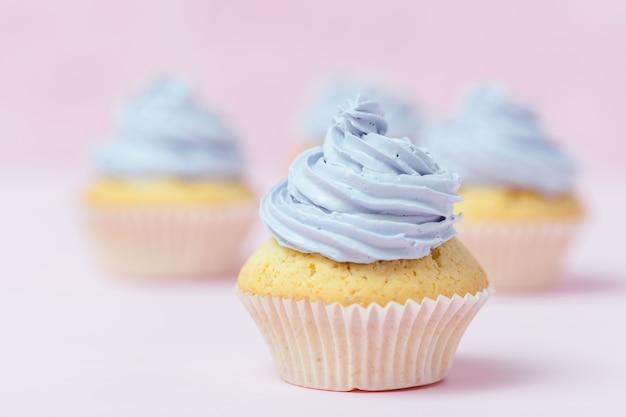 カップケーキは、パステルピンクの背景に紫のバタークリームで飾られています。