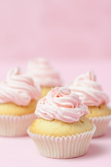 パステル調のピンクの背景にピンクのバタークリームで飾られたカップケーキ。甘い美しいケーキ