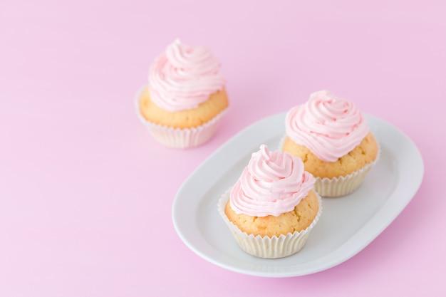 カップケーキはパステル調のピンクの背景にピンクと紫のバタークリームで飾られています。