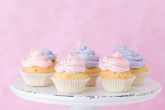 ぼろぼろのシックなスタンドにバイオレットとピンクのバタークリームで飾られたカップケーキ
