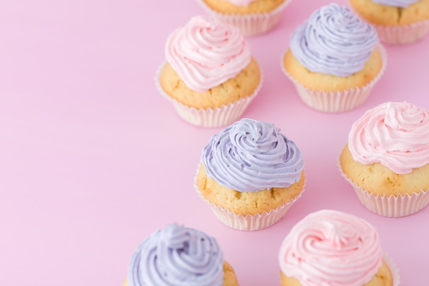パステルピンクの背景上面に紫とピンクのクリーム色の立っているとカップケーキ。