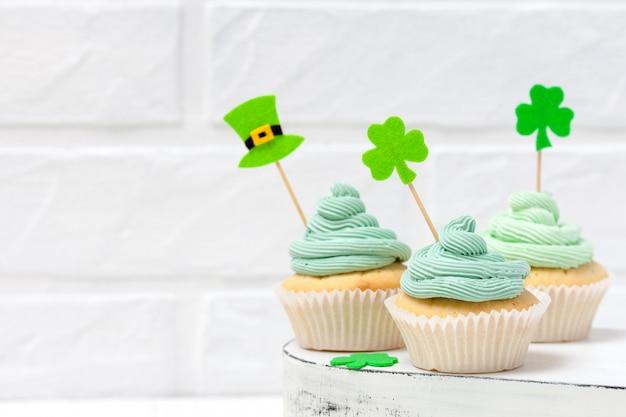 聖パトリックの日のテーマカラフルな水平方向のバナー。緑のバタークリームで飾られたカップケーキ