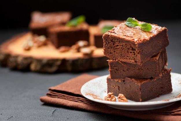 クルミと白い皿の上のスタックのチョコレートブラウニースクエアピース