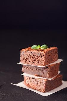 ミントで飾られたクルミと白いプレート上のスタックのチョコレートブラウニースクエアピース