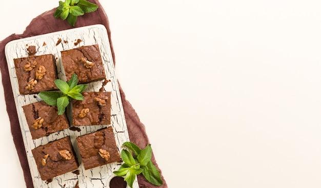 レトロなボードにクルミと葉を意味するブラウニーの甘いチョコレートデザート