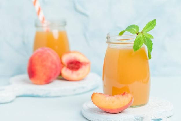 新鮮な熟したフルーツとミントグリーンのガラス瓶の中の桃のスムージーブルーパステル調の背景に残します