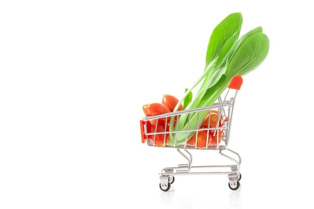 赤いトマトとベビーボクチョイ買い物カゴで。良い健康のための健康的な食べ物。野菜。