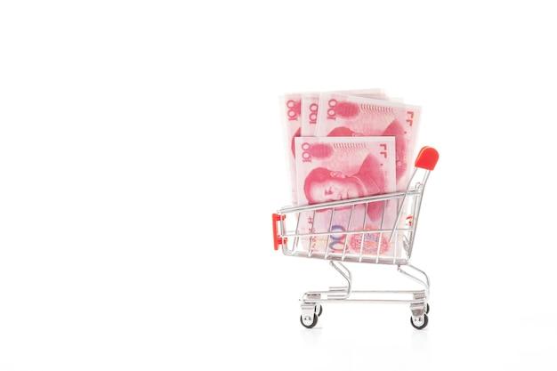 白い背景に小さなショッピングトロリーで中国の紙幣。財務コンセプト。