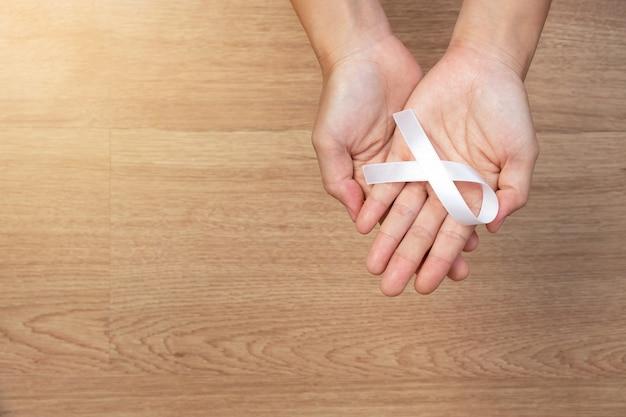 女性の手は、木製の背景に白い弓、白いリボンを保持しています。