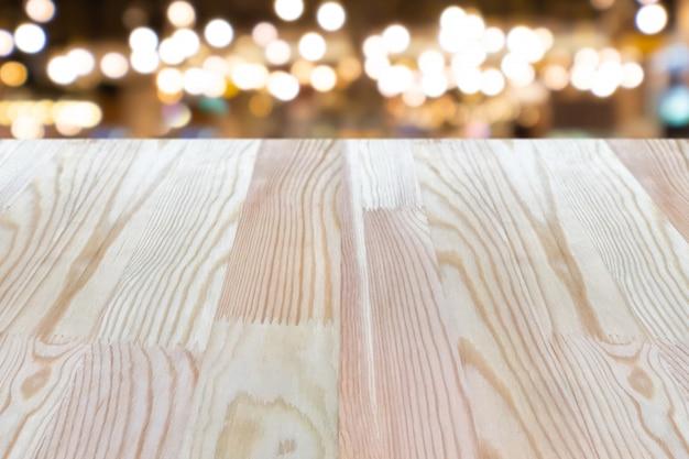 ぼかしの背景の上に空の木製のテーブルは、モックアップすることができます