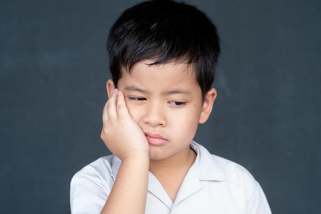 アジアの少年は欲求不満と怒っている、黒の背景に分離を示します。