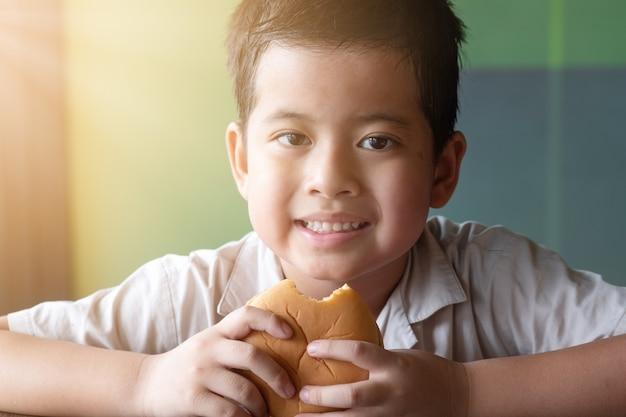 アジアの男の子の肖像画はハンバーガーを食べています。健康の概念