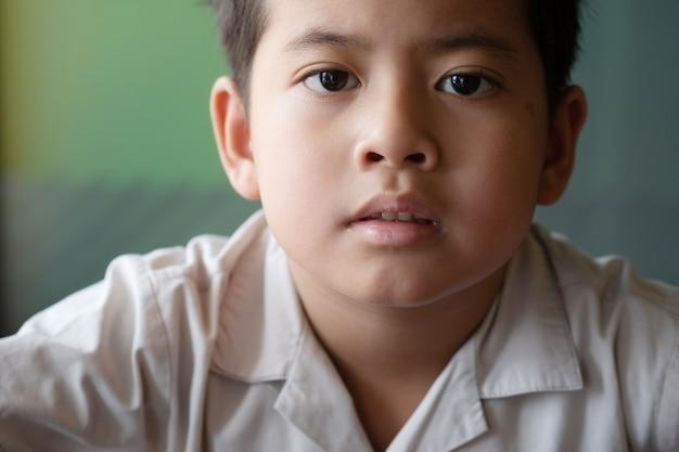 感情を示すアジアの少年を閉じる