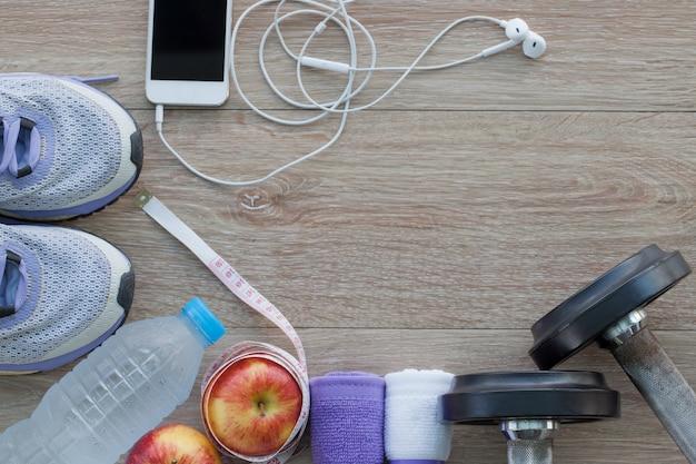 ランニングシューズ、タオル、水のボトル、リンゴ、測定テープ、携帯電話、ダンベルとフィットネスコンセプト上から見る