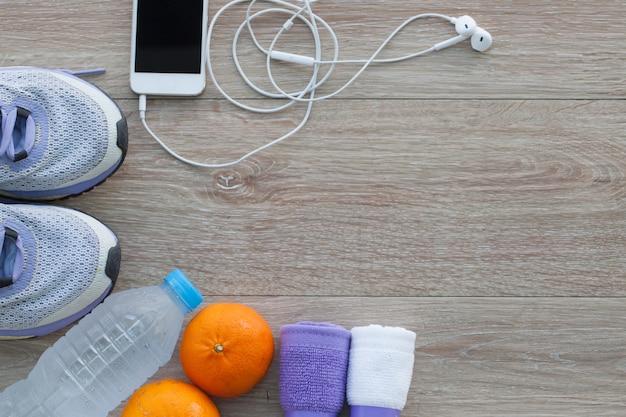 ランニングシューズ、タオル、水、オレンジ色、携帯電話のボトルを持つフィットネスコンセプト上から見る