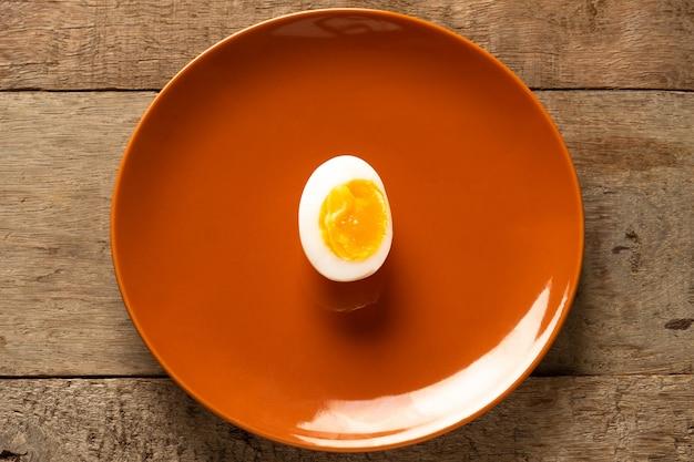 木製のテーブルの上の茶色のセラミック皿の中ゆで卵
