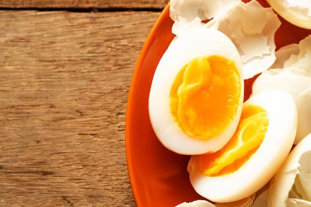 木製テーブルの上に茶色のセラミック皿に中ゆで卵と卵の殻