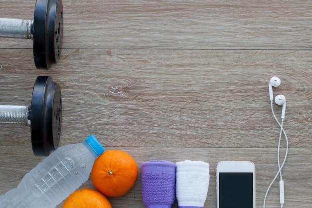 タオル、水、オレンジ、ダンベル、携帯電話のボトルとフィットネスコンセプト。上から見る