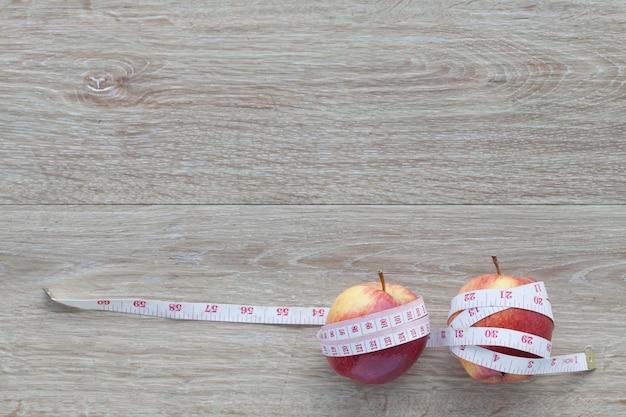 赤いリンゴの芯と測定テープ。体重管理の概念果物で減量、ダイエットの概念、過度の減量の悪影響。