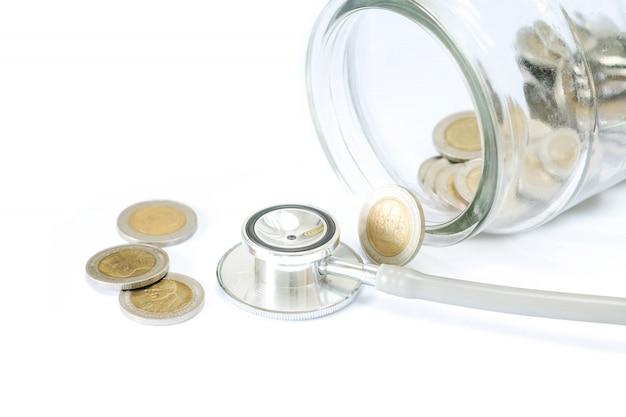 ボトルと白い背景の上のコインの聴診器。ファイナンスヘルスチェックまたはビジネス、財務分析、監査または会計のコストの概念。