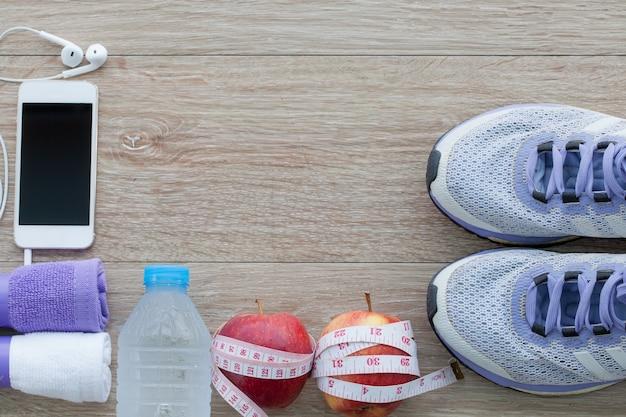 ランニングシューズ、タオル、水、リンゴ、測定テープ、携帯電話のボトルとフィットネスコンセプト上から見る