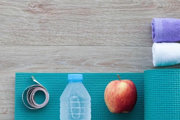 タオル、水、リンゴ、メジャーサイズ、ヨガマットのボトルとフィットネスコンセプト。上から見る