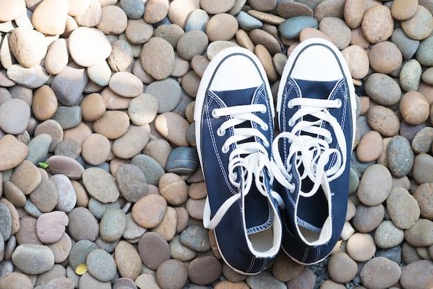 青いスニーカー、石の床、上から見える。