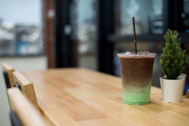 ミントとチョコレートの冷たい飲み物をプラスチックガラスに、木製のテーブルに置く