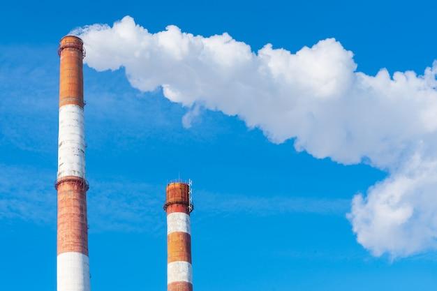 植物のパイプは有害物質を大気中に放出します。空を背景にクローズアップ。