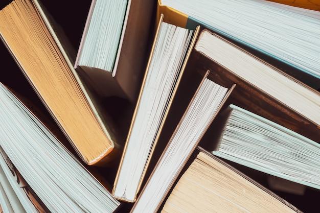 濃い背景の上に厚い開いた本がたくさん並んでいます。学校に戻る。教育の背景
