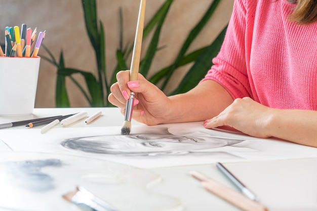 若い女の子がホームスタジオで黒の絵筆で男の肖像を描きます。