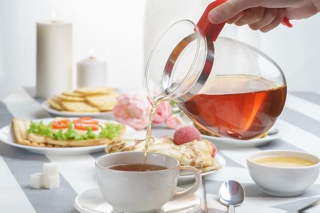 軽いバックグラウンドでのサンドイッチと紅茶の新鮮で美味しい朝食。