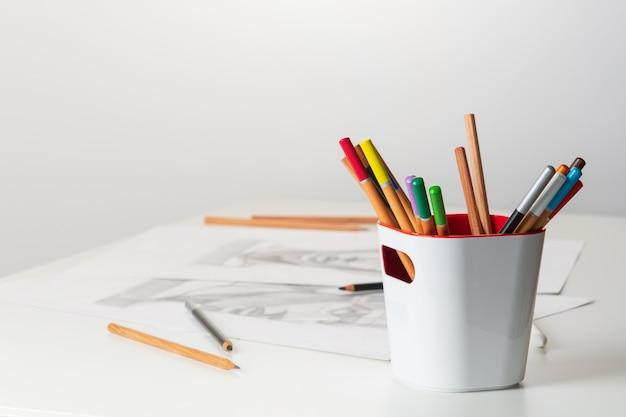 テーブルの上には色鉛筆があり、グラフィックスのシートが描かれています。