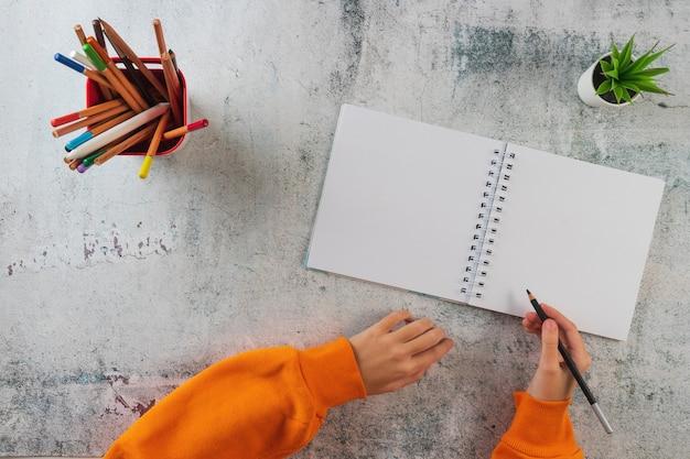 若い女の子がアルバムに描く準備をしました。テーブルの上に色鉛筆、ノート、手があります。