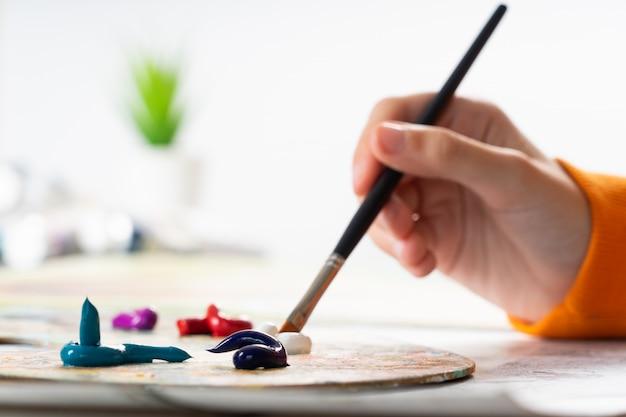 若い女の子が絵筆を手に持ち、それを油絵の具に捨てます。パレット上で色を混ぜ合わせるプロセス。