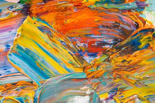 パレットのクローズアップにオイル塗料を混ぜ合わせた、明るくジューシーで多色の抽象化。