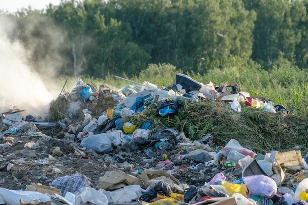 Городская свалка с разным мусором горит в солнечный летний день