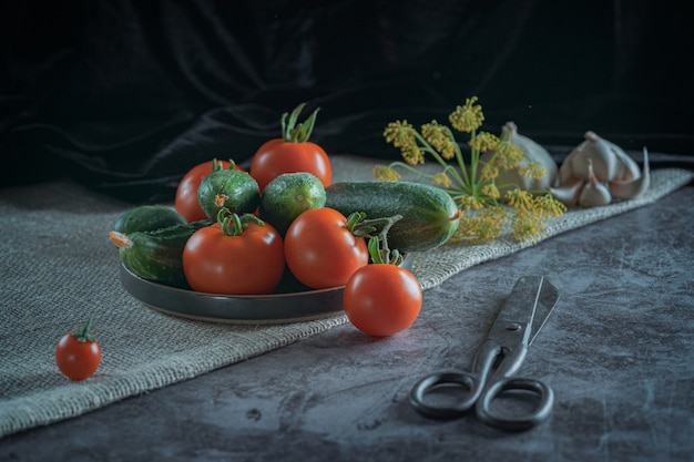 新鮮な野菜の素朴な静物:赤いトマト、緑のキュウリ、ニンニク、暗い背景にディル。