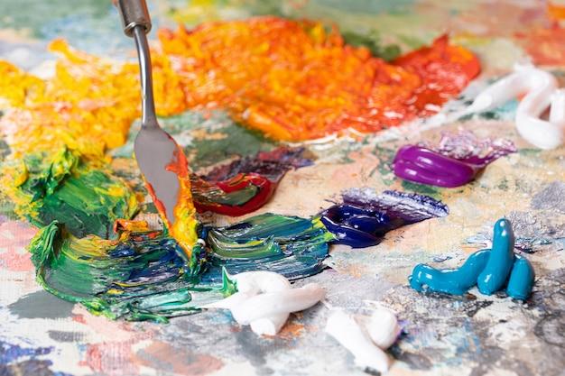 パレットクローズアップの油絵具の混合の明るく、ジューシーな、マルチカラーの抽象化。