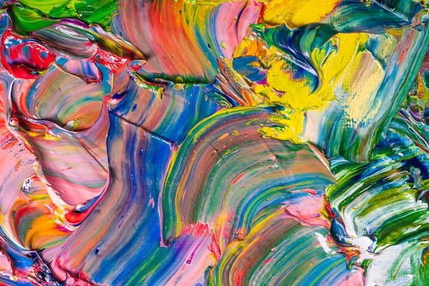 Различные яркие цвета масляных красок смешиваются на палитре крупным планом.