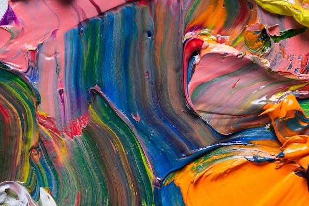 さまざまな明るい色の油絵の具がパレットのクローズアップに混在しています。