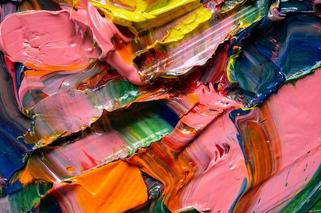 芸術的な背景。さまざまな明るい色の油絵の具がパレットのクローズアップに混在しています。