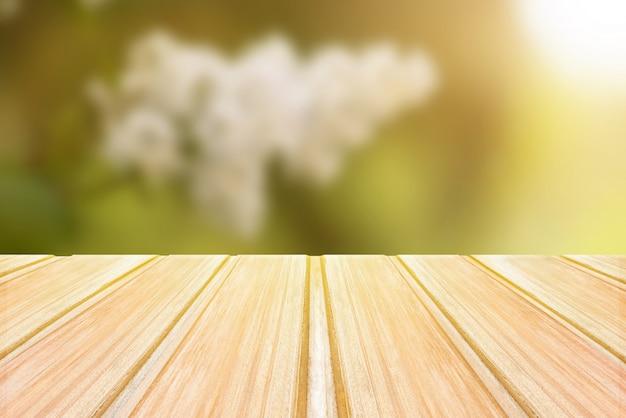 ぼやけた春の背景、花と公園のボケ味を持つ空の木製テーブル