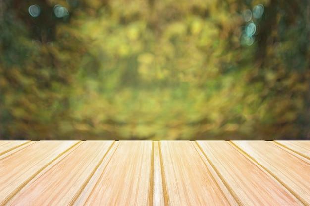 背景にぼやけている都市公園の空の木製テーブル。コンセプトパーティー、製品、春