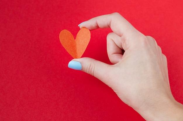 赤の背景に赤いハートを持っている手。バレンタインデーの背景