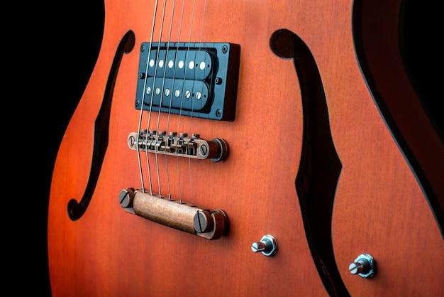 ハムバッカー付きホロウボディエレクトリックギター。マクロ撮影、黒背景、暗いキー