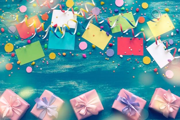 ホリデー色の紙吹雪の蛇行紙のギフトボックスのためのお祝いの明るい青色の背景の装飾