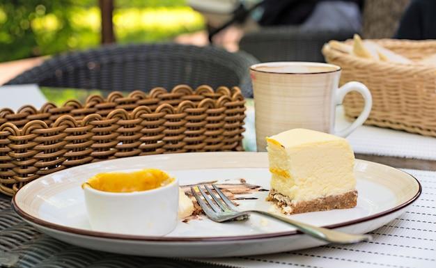 大きな白い皿、マンゴーソースとクリーミーなチーズケーキ